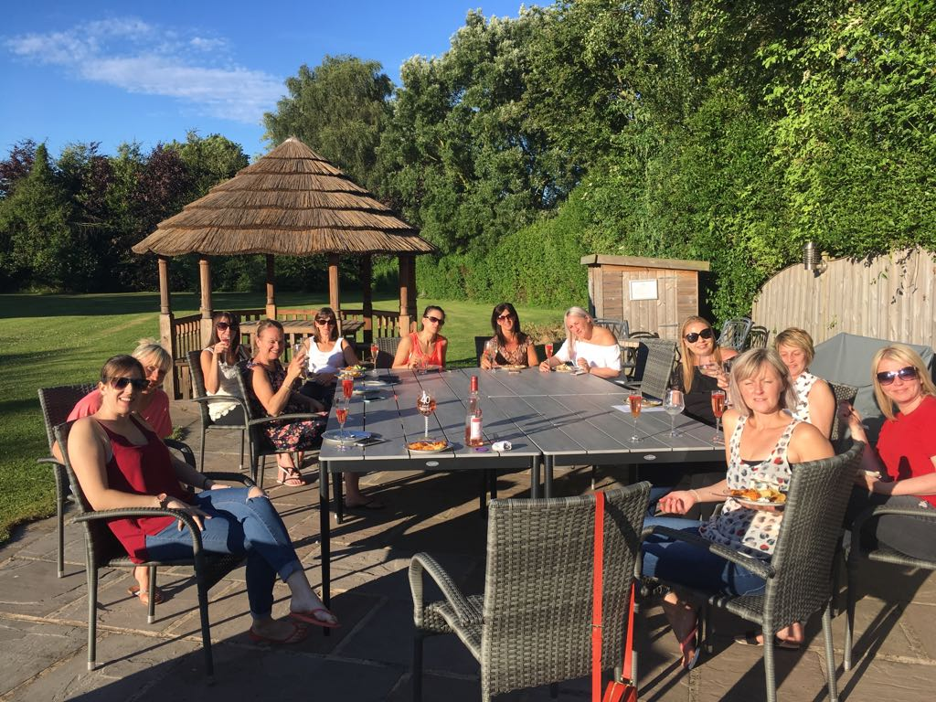 Guests Enjoying Alfresco Drinks On the Outdoor Patio Homes for hen parties